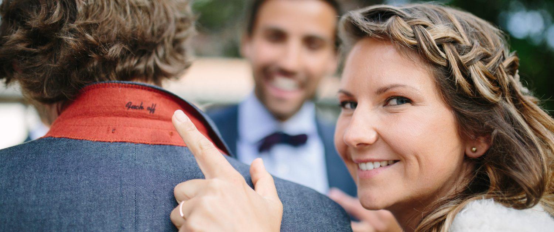 La mariée indique l'inscription sur le col de la veste de son mari